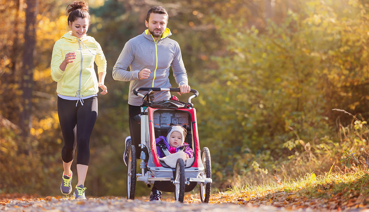 Two parents jogging with their baby in a stroller.
